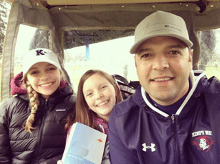 Jason with his two daughters, Isabelle and Aubrey, coaching at a KWHS golf match.