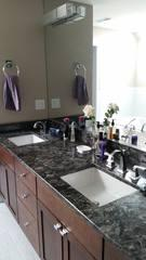 This bathroom remodeling project features twin sinks and a dark marble countertop.