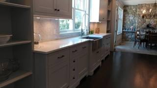 The white kitchen countertops provide a clean, modern look and complement the cabinets.