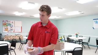 Production Team Member David begins to place a roll in individual bags for each meal.
