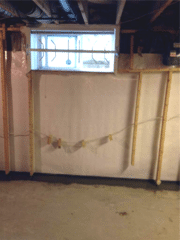 A view of the Waterproofing system working together. Within this photo there is the WellDuct® Window Well Drain behind the CleanSpace® (white plastic material) that is tied into the WaterGuard® below.
