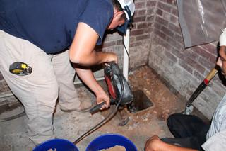 Production Team Leader Diego Sanchez breaks up the concrete around the existing pump for removal.