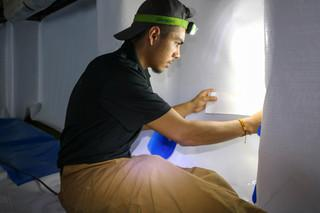 Production Team Member Estevan works diligently to secure the CleanSpace material to the wall for the perfect fit.