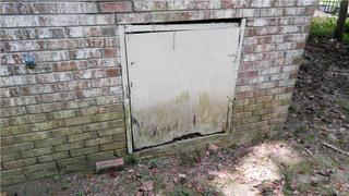 Homeowner Gloria's crawl space door was not assisting in preventing water from entering because of its condition.