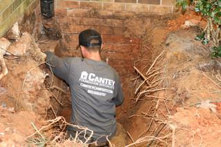 Production Team Member Robert clears a path for the Helical pier to be installed on the side of the porch.
