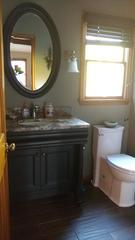 Updated bathroom featuring new hardwood floors and matching vanity.