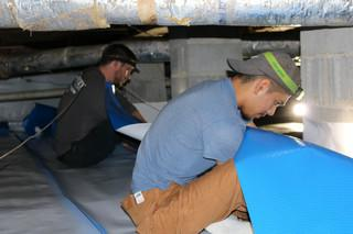Team Members Estevan and Jonathan make sure the CleanSpace material is measured just right to cover this area of the crawl space.