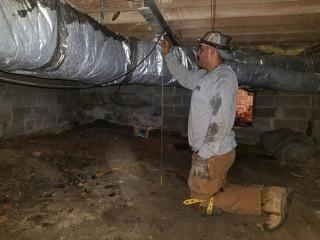 Production Team Leader Sixto measures the space in the crawl space to cut the SmartJack for the perfect fit.