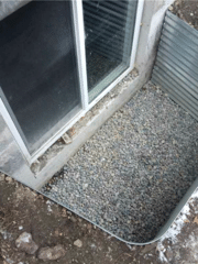 A view of the homeowner's window well. In order to prevent flooding a WellDuct® Window Well Drain was installed to control the excess water. The excess water is guided towards the installed sump system within this homeowner's basement.