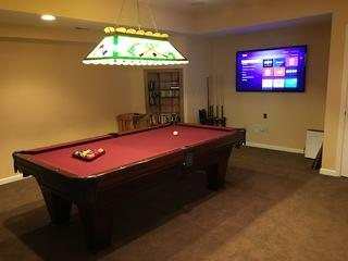 TV installed next to pool table.
