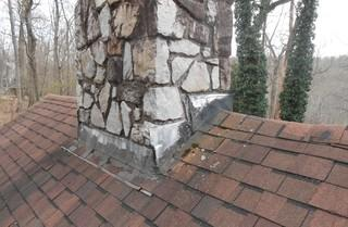 You can see the wear and tear of these 27-year-old shingles and chimney flashing.