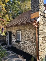 Installed on this beautiful stone home was copper chimney flashing and copper half round gutters.