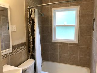 Photo of the new tile installed above the bathroom tub.