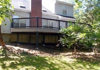 This deck features Timbertech Ashwood decking with an espresso picture frame and black builder railing.