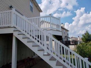 This deck uses Timbertech Sandy Birch decking and white vinyl railing.