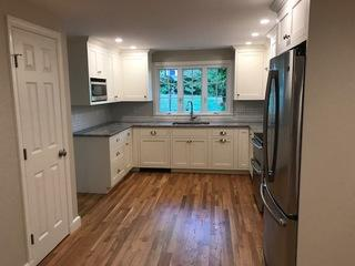 Real hardwood flooring and white shaker cabinetry complete this kitchen remodel.