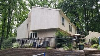 This photo shows a side and front view of the home's wood siding.