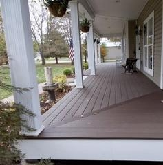 This O'Fallon, Illinois deck features Timbertech Rustic Elm decking with white fascia on the porch and black builder railing with Rustic Elm top cap.