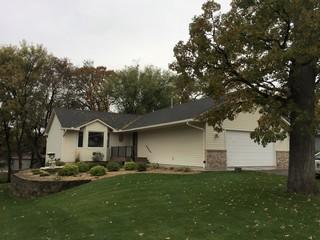 LeafGuard® gutters and downspouts in color eggshell installed on charming ranch home with attached garage in Elk River Minnesota.