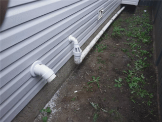 On the exterior of the home is the sump pump's discharge line and the radon mitigation discharge line