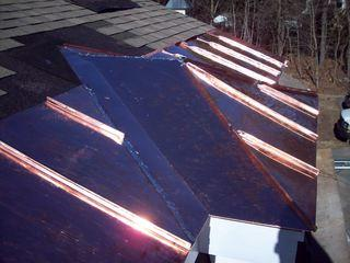 Our craftsmen installing copper panels into the edge of the roof.