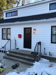 """LP SmartSide 6"""" smooth cedar wood texture siding in White, with CertainTeed Northgate Roofing in Moire Black with Harvey Majesty Black windows and a new Therma Tru front door in Black"""