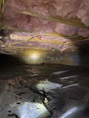 A dark, messy crawlspace in need of encapsulation.