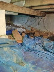 Concrete floor with blue tarp used as a moisture barrier