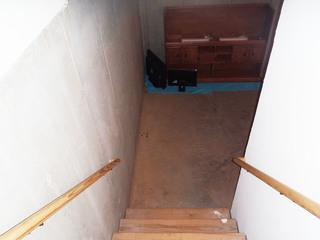 View looking down the stairs, into the old concrete basement