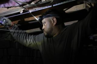 Cantey Team Member measures the length needed to cut beams for SmartJacks installation and support.