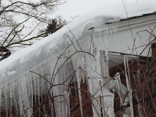 Thick icicles hanging from roof eaves could indicate a serious ice dam problem. Observe how the freezing pattern seems to pour off of the roof.
