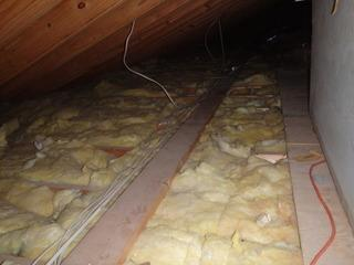 This photo captures the old and dirty attic insulation. After the many years attic insulation sits in the attic, it can collect dust, dirt, bugs, etc.