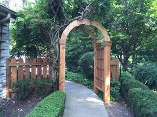 This view shows the arbor we crafted for this project, which will support the beautiful gardens and shrubs nearby.