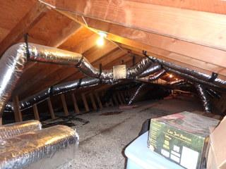 This photo captures the attic before Dr. Energy Saver Delmarva began to cap the fiberglass insulation with TruSoft blown cellulose insulation.