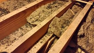 This photo captures the old and dirty insulation in this homeowner's attic.