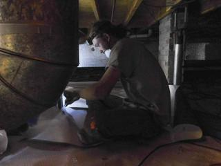 Production Crew Member Ethen cuts the encapsulation material to fit the crawlspace perfectly.