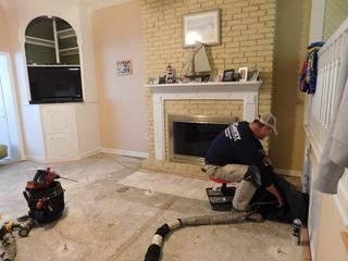Customer Vincent C.'s living room, which had the concerned spot in the slab where it leaked.  Production Crew Foreman and PolyLEVEL Technician TJ Harden injected the polymer substance underneath the slab to ensure stabilization.