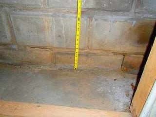 Without x-ray glasses, our inspectors can't tell the exact thickness of the basement floor. The best way to get a close estimate is to measure the bottom block in the wall. These blocks are 8 inches tall. If he can see more than 4 inches above ground, he knows that it isn't safe to install a below ground drainage pipe system. If he can't see the wall because the basement is finished, he will look for a closet or utility room like this picture shows.