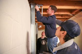 Production Crew Foreman Israel Santana shows Production Crew Member Samson how to install power braces.