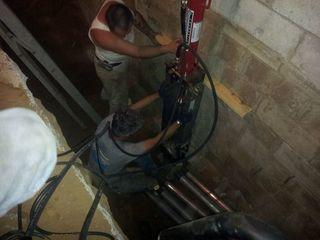 Adirondack Basement Systems installing Helical Piers to fix the sinking foundation in a home in Clifton Park, NY