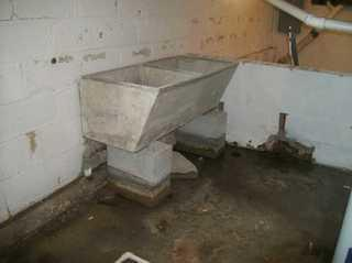 You generally won't find wash basins attached to the walls in modern basements. Also, the large cast iron pipes on the floor are a sign of older construction. These things present a slight challenge when designing a waterproofing system. This photo was from the day of the initial inspection. The stains on the concrete blocks let the inspector know that water has been high enough to leave a dirt ring behind. It is clear evidence of a major water problem.