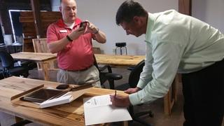 Owner William Cantey signs the Statement while Jacob Porter takes a picture.