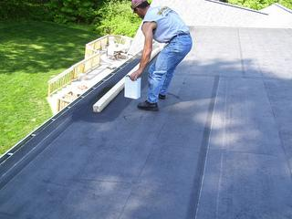 Here we have the crew in midst of installing a flat rubber roof on this home.