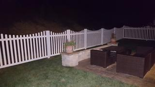 This a photo of the white picket fence & the homeowners outside entertainment area.