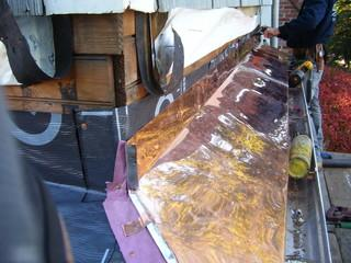 With the siding removed, the crew has installed ice & water shield and then attached the copper ledge over it.