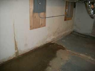 "The wet spot on the floor was pretty much always there, according to the Easton, Maryland homeowner. The dirty and rust colored stains on the wall are actually cracks that leak during storms. DryZone usually installs a few feet of CleanSpace liner on the walls when adding a drainage system to a basement. This prevents cracks like this from ""jumping the drain"" and spraying on the floor after installation."