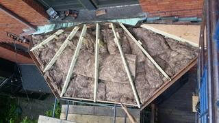 The old roof has been removed, and both insulation and a new wood frame have been installed above the dormer.