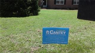 Marjorie stakes Cantey's sign in her front yard after her great experience with our production team.