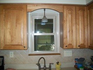 Energy Swing Windows installed tan vinyl windows throughout this home, including this window above the sink in the kitchen.