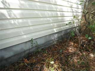 The crack is running along the bottom of the house which is a sign of a cracked foundation.